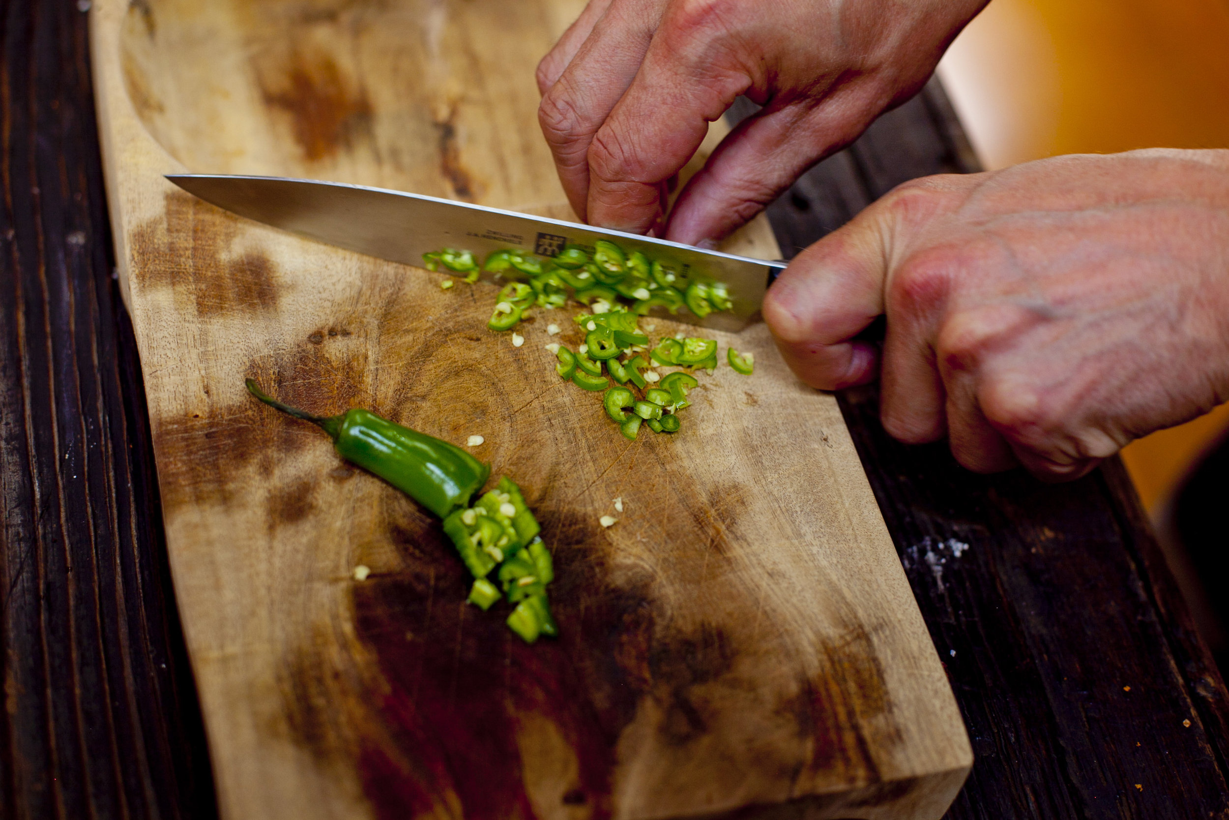 Chopping hot peppers.