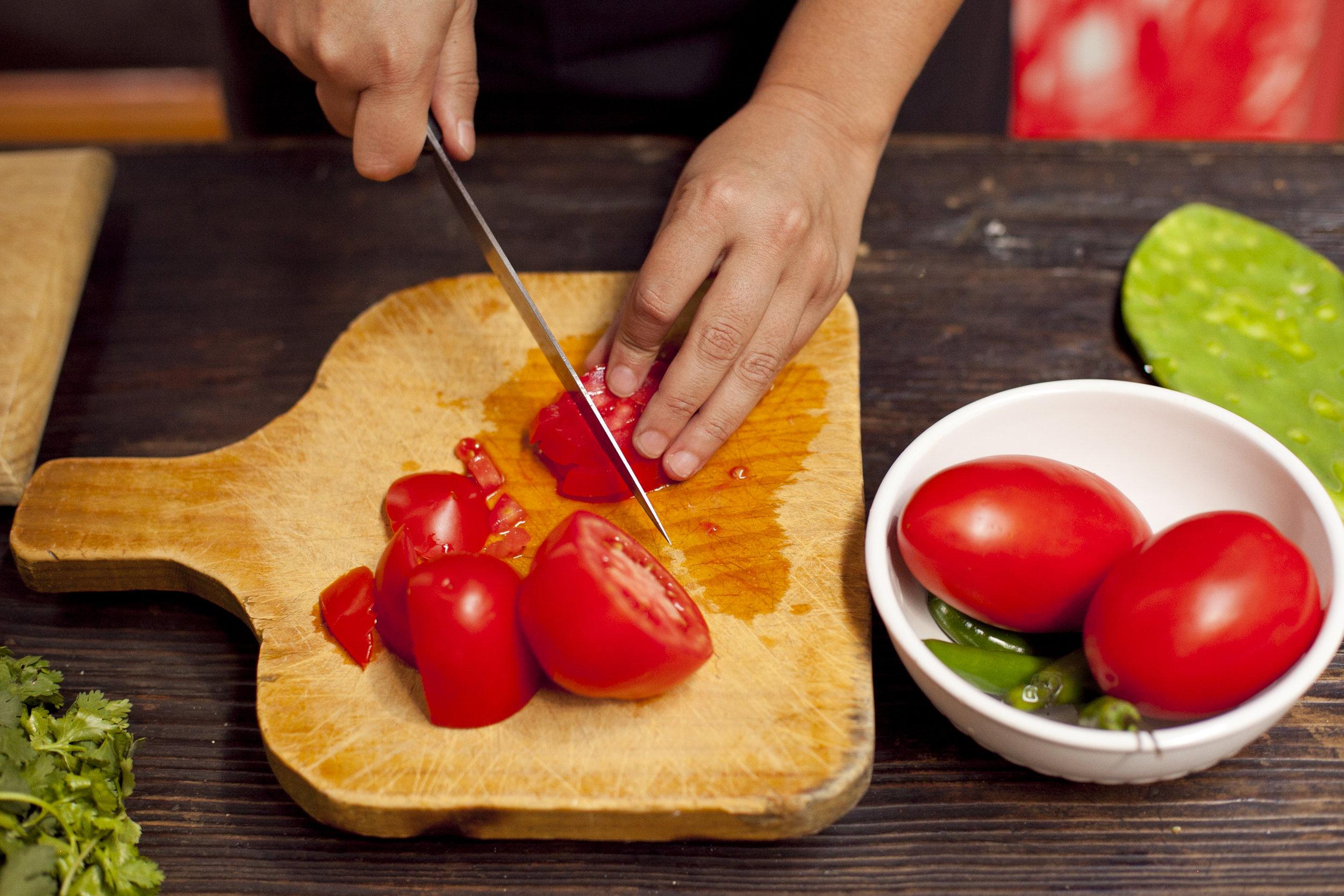 Chopping tomatoes.