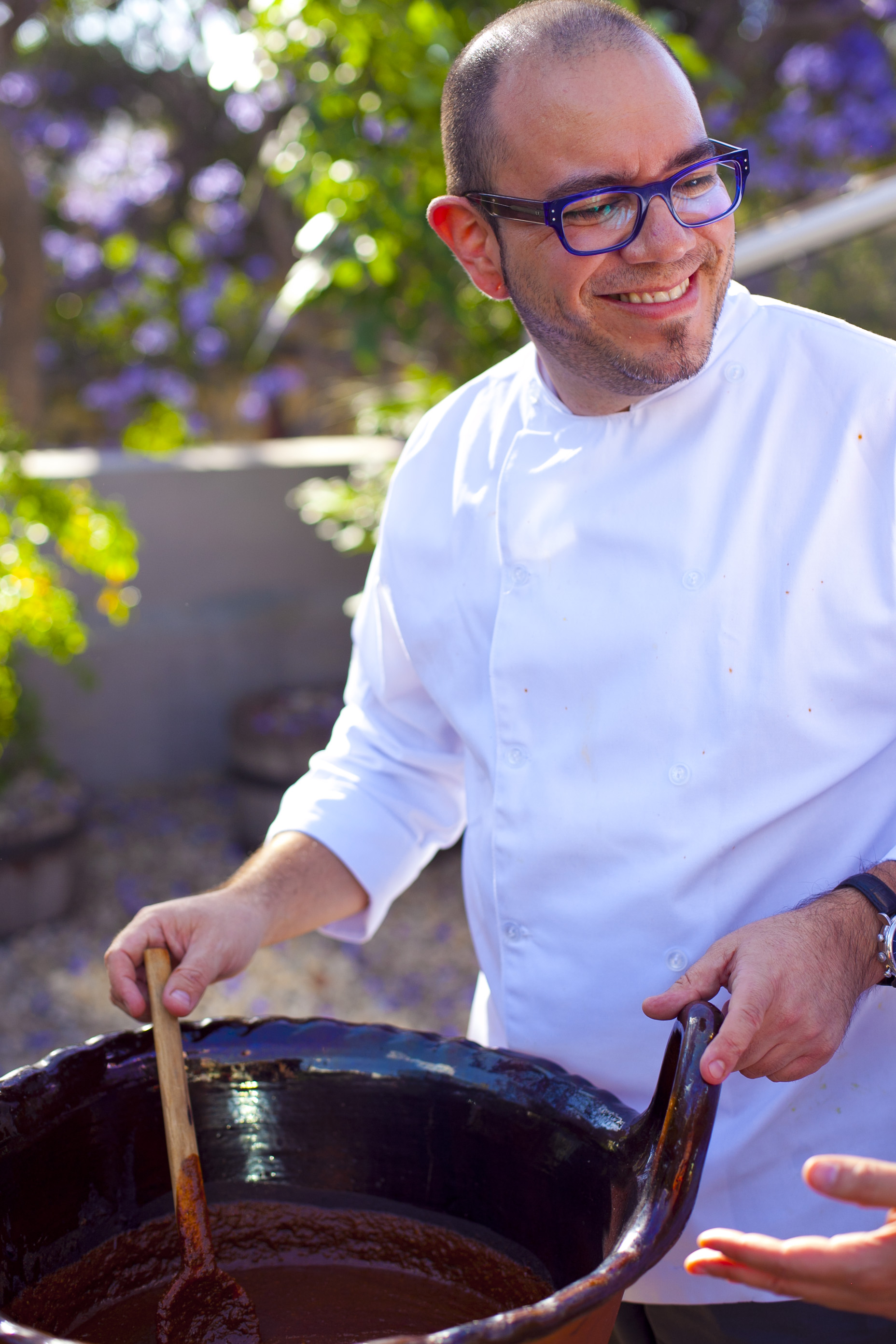man stirring a big bowl of Mexican mole