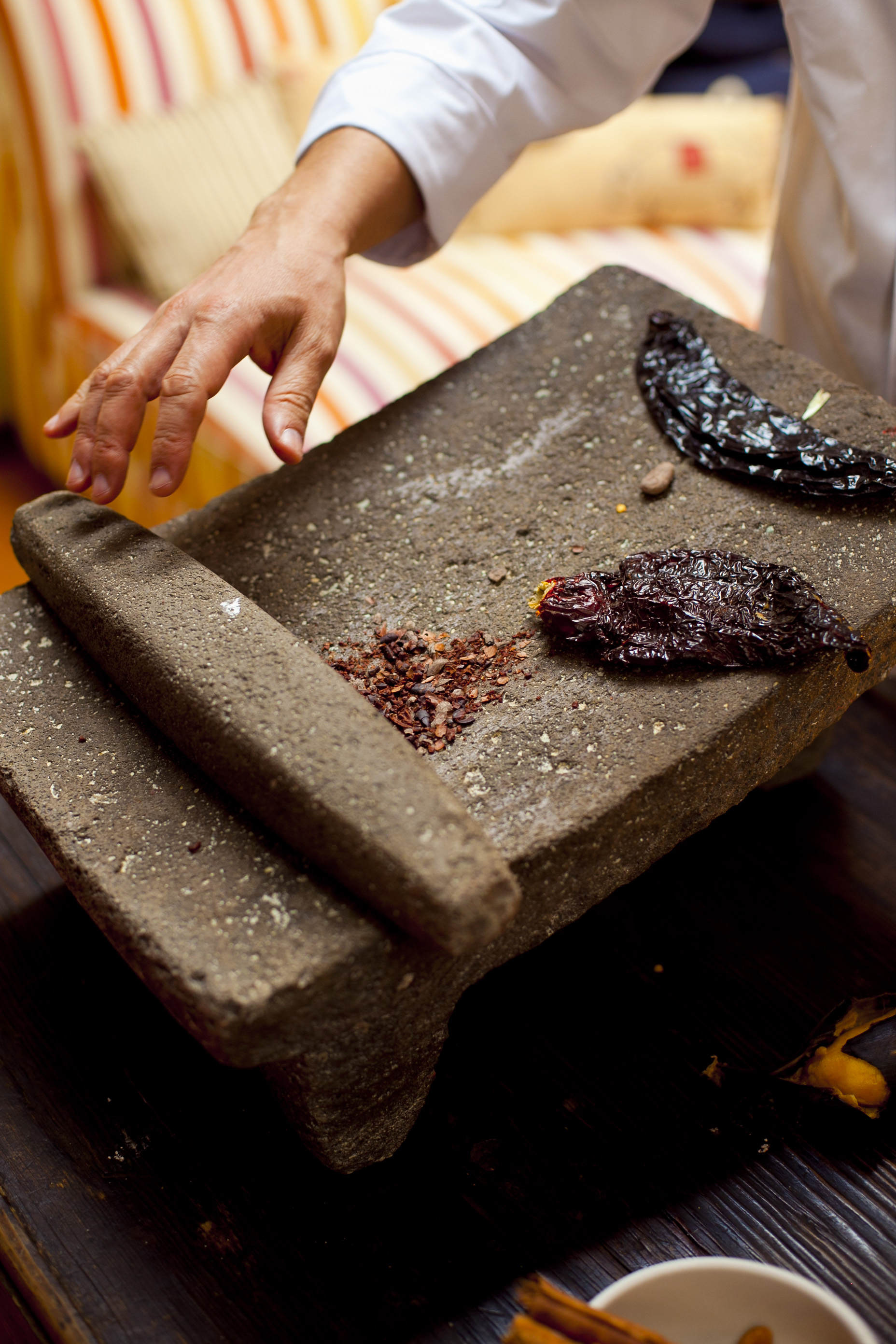 crushing chilis on a stone metate