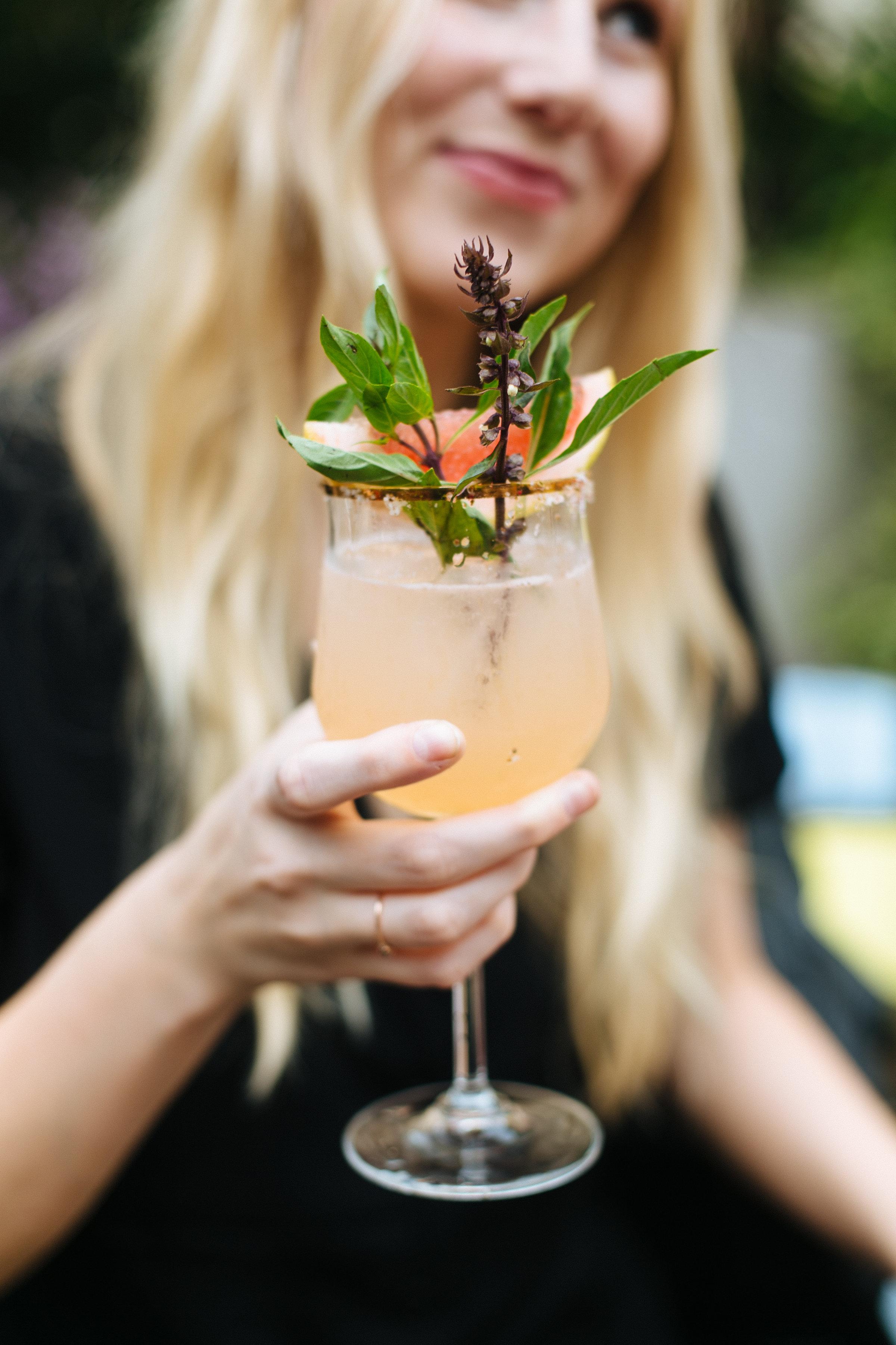 Bri Emery holding a Altos tequila cocktail at Casa Jacaranda.