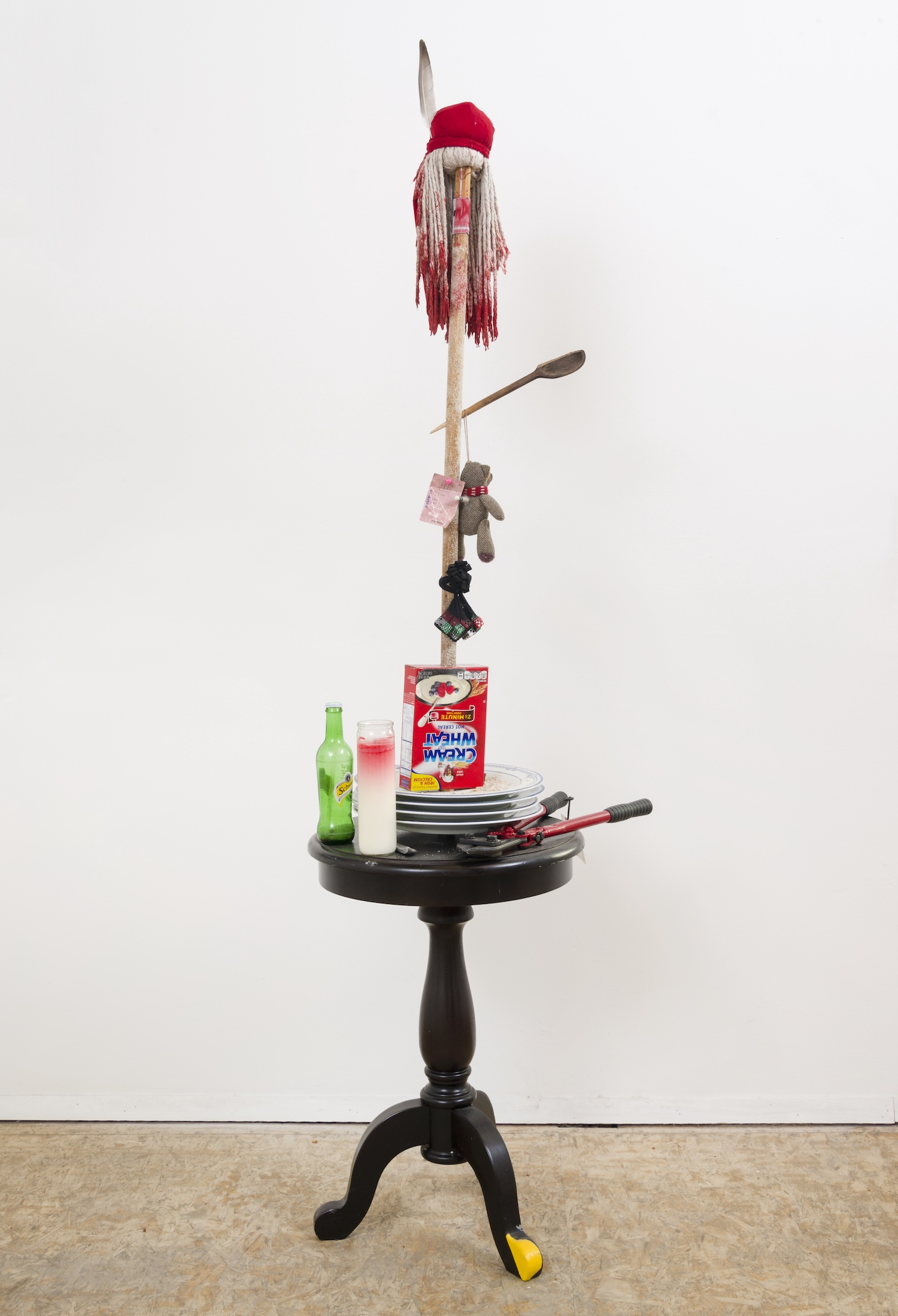 Daniel Gaitor-Lomack  Flesh Wound , 2016 mop, red du rag, incense, Cream of Wheat box, Cream of Wheat, broken wood spoon, teddy bear, crayon, feather, acrylic, metallic spray paint , Vaseline, handmade plates (Japan), wood table, glass candle, glass bottle, reverse clothing label, NJ Transit Air train ticket, thumb tack, dice, hair net, bolt cutters 80 x 24 x 20 in.
