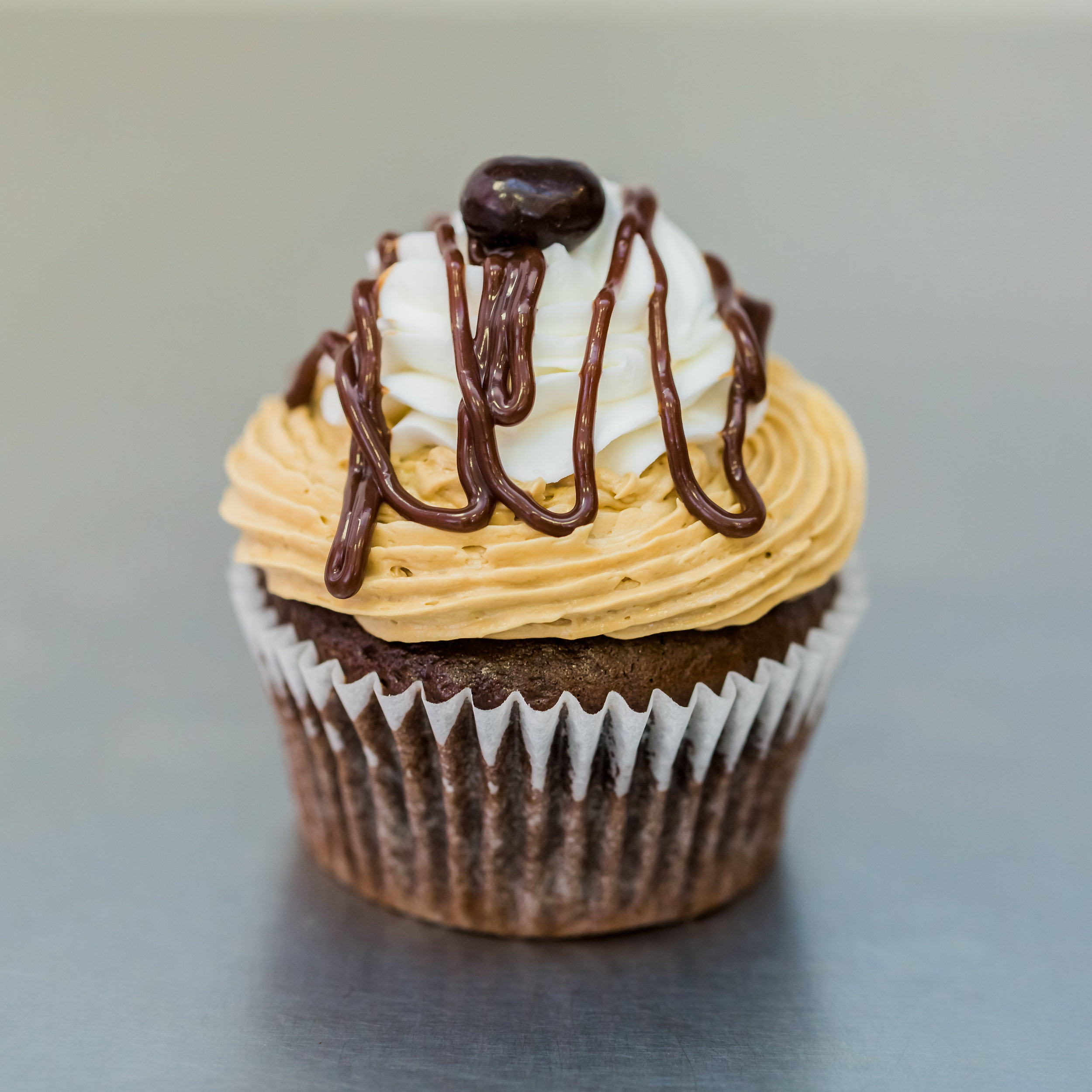 Mocha Latte - Chocolate cake frosted with espresso buttercream and whipped cream, garnished with chocolate ganache drizzle and an espresso bean