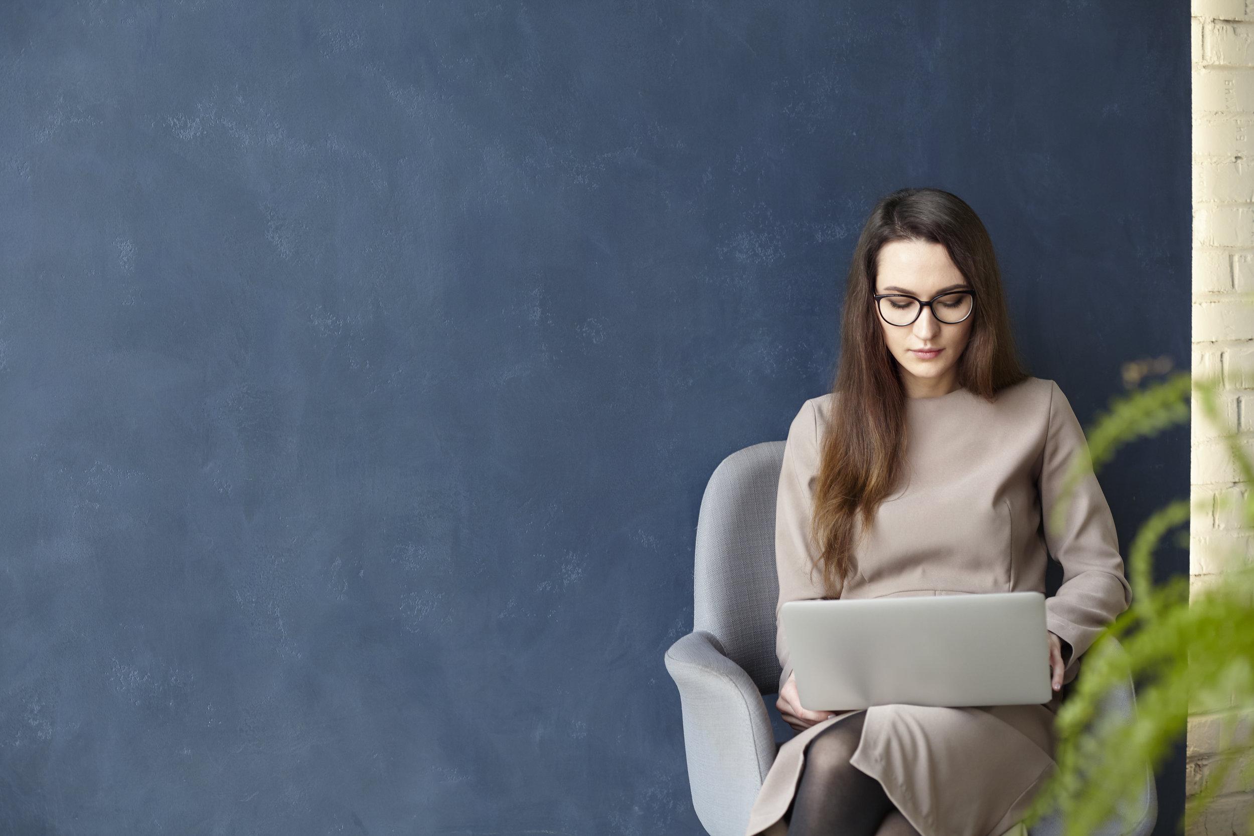 Beautiful-businesswoman-working-on-laptop-while-sitting-in-modern-loft-office.-Dark-blue-wall-background,-day-light-653222072_6000x4000.jpeg