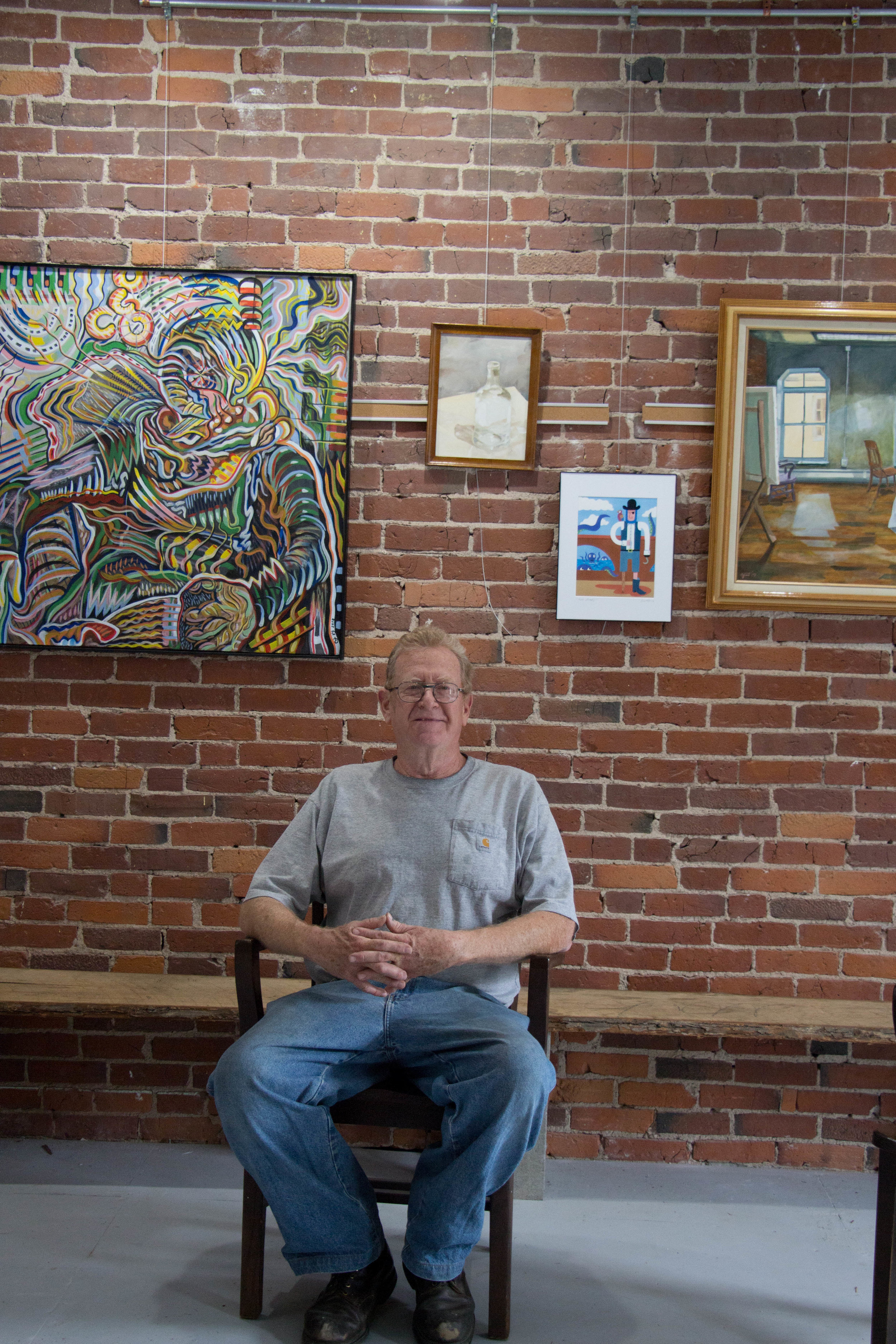 Mike Gent sits with works of art that represent the in-house artists at Cattywampus.