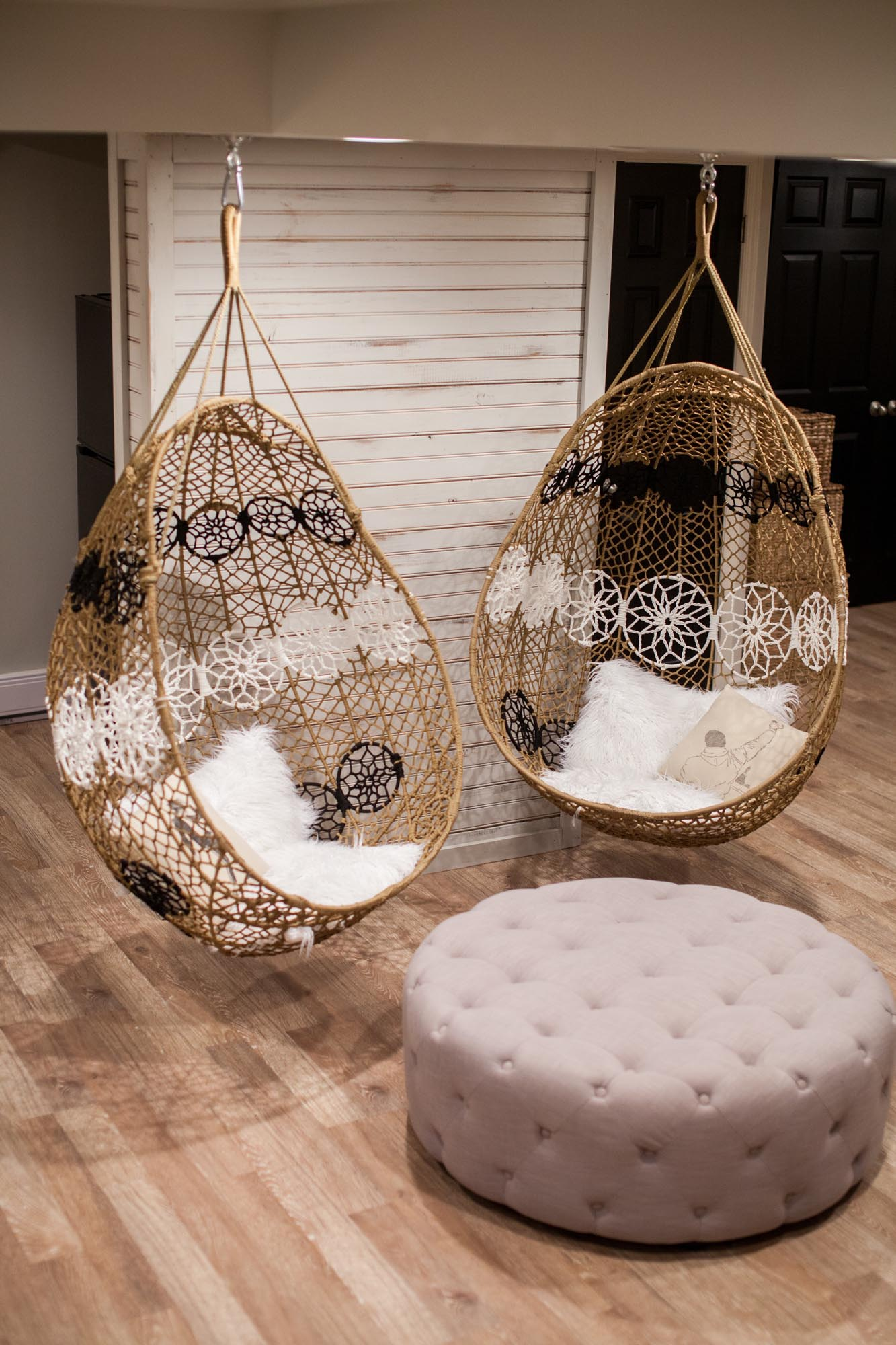 Hanging wicker chairs and round cushioned ottoman