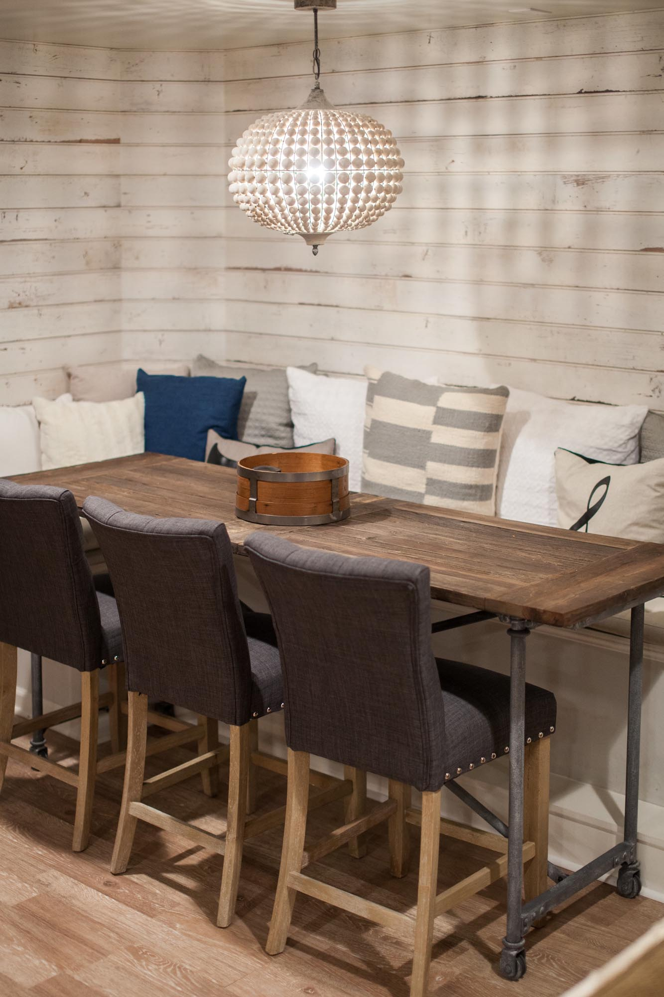 Wooden table with comfortable seating and shiplap walls