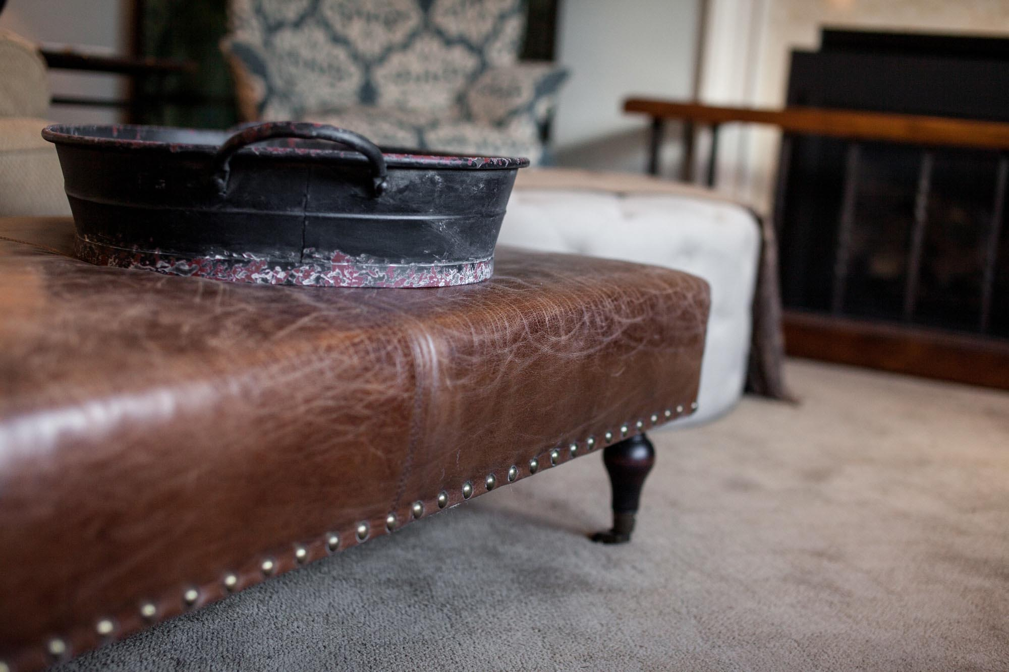 Brown leather ottoman with metal tray and comfortable seating