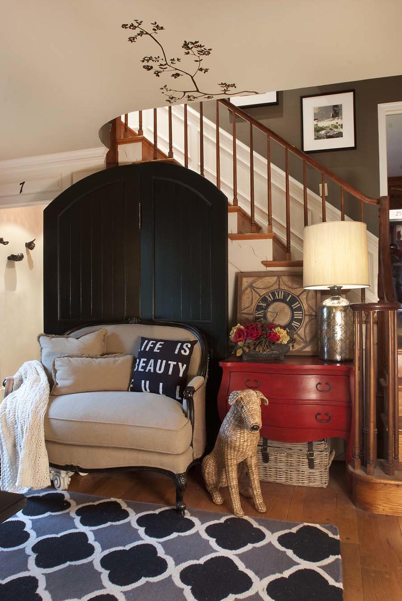 Comfortable seating area with soft loveseat and burlap style stuffed dog and red dresser