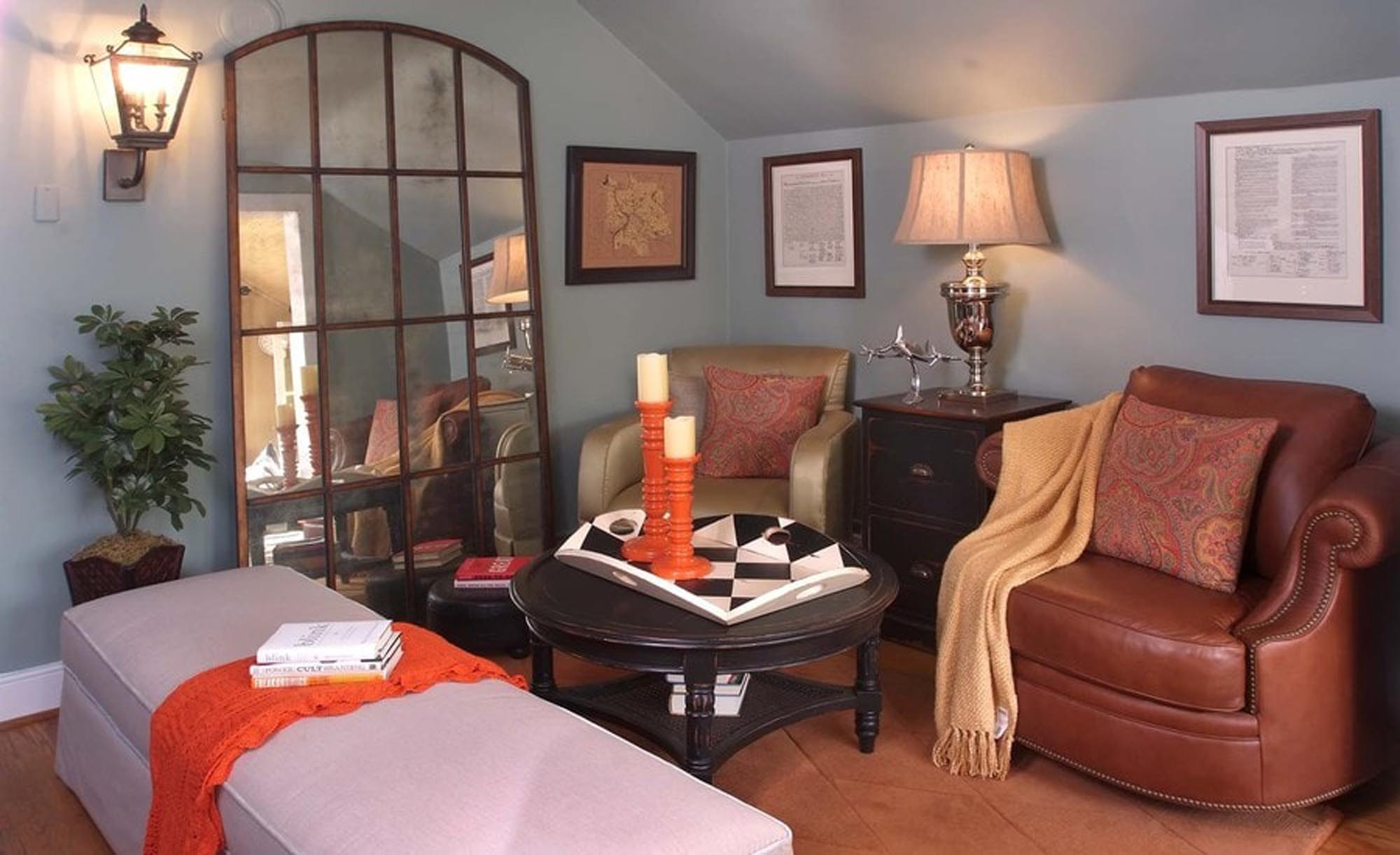 Long violet colored ottoman with antique mirror leaning against wall