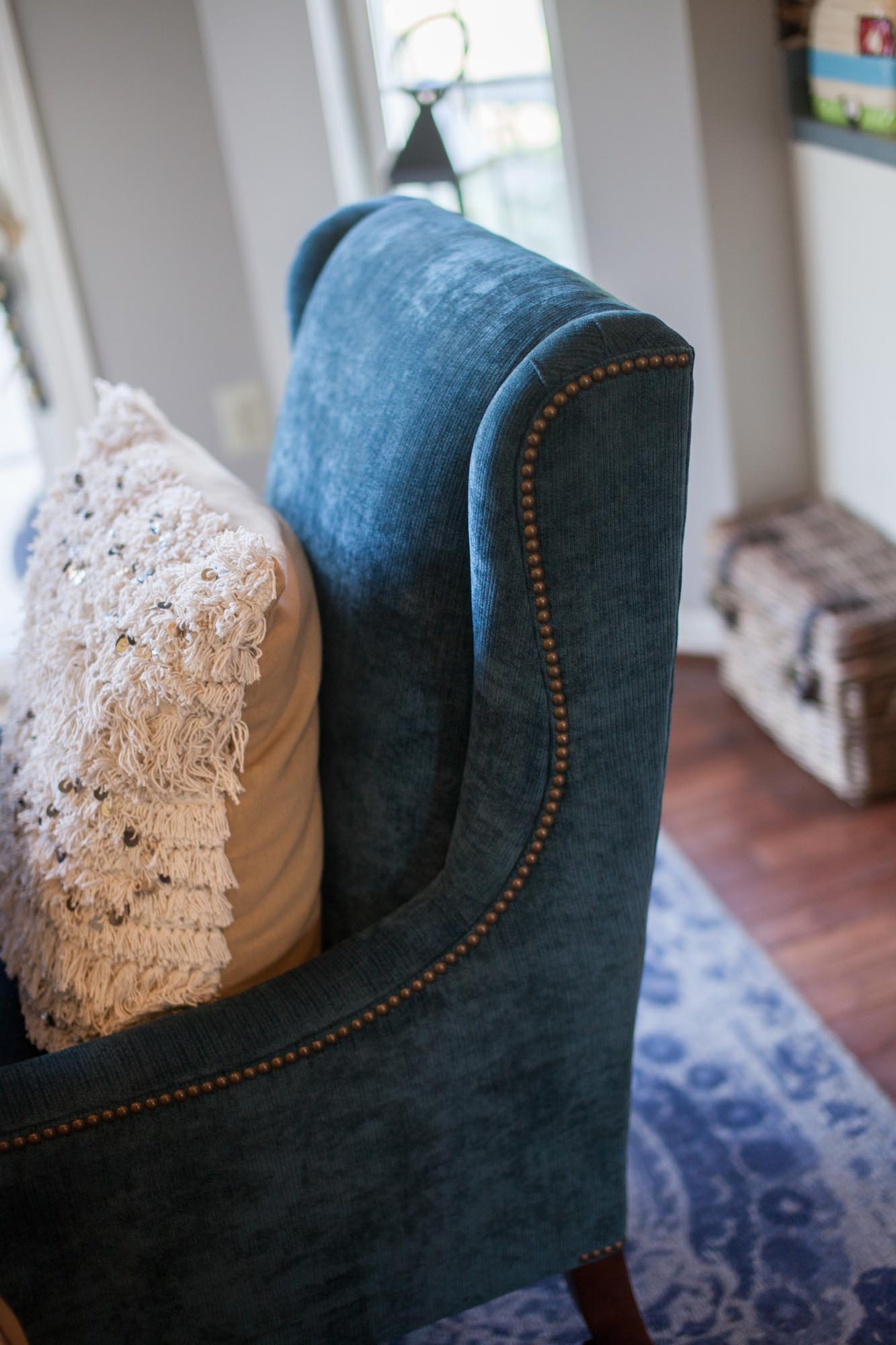 Blue stuffed chair with beige colored stuffed pillow