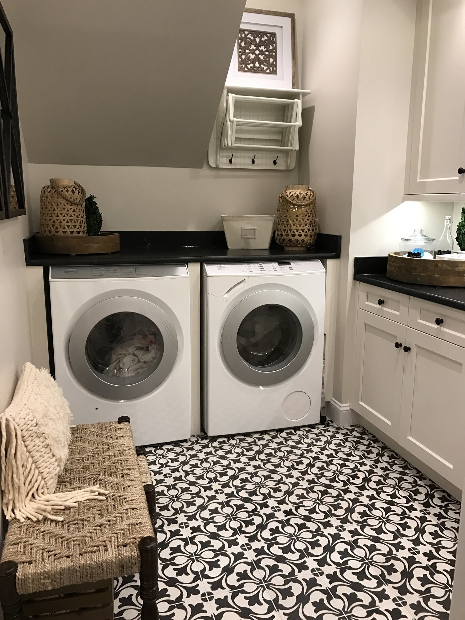 Modern mud room with washing machine and black and white patterned floor