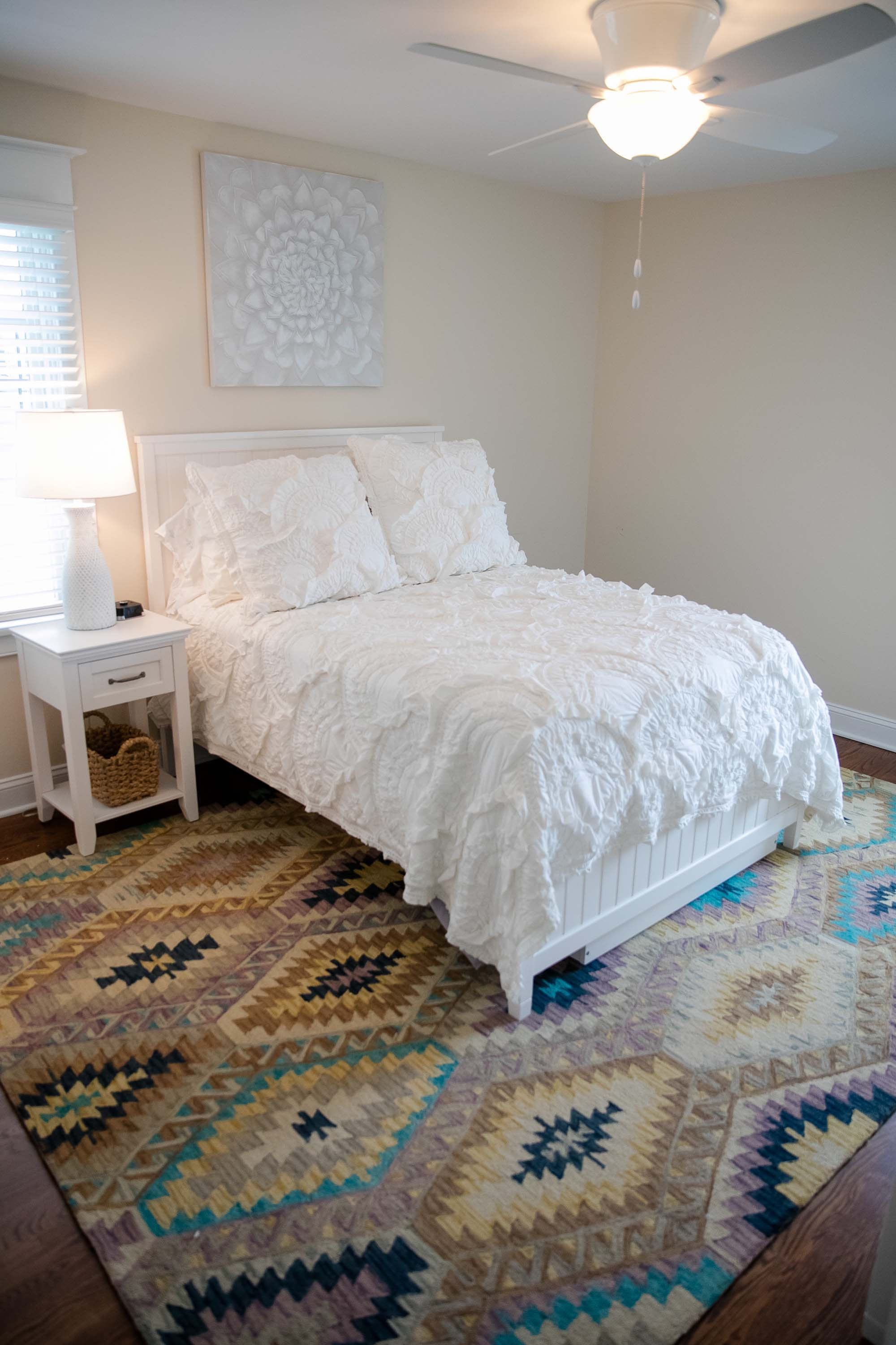 White bed, resting on tribal print area rug