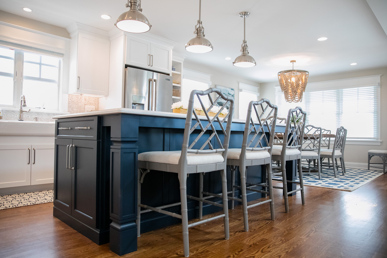 Modern style blue kitchen island and light colored chairs