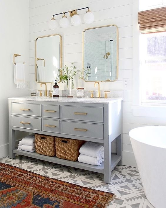 I've said it before + I'll say it again - don't be afraid of pattern in the bathroom! It's one of the only spaces in your home that you can concentrate details without overpowering since it has limited furniture. Love this vintage statement rug layered over the geometric tile pattern.  Design by @amylindinteriors