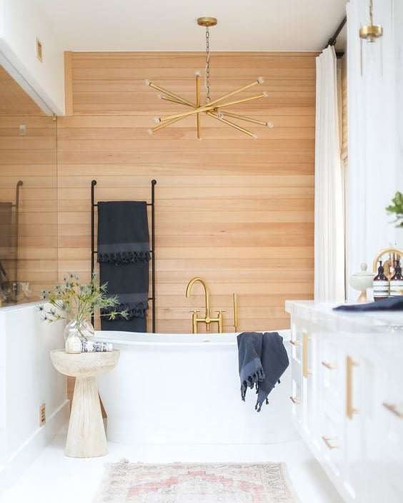 I've been seeing more and more natural, warm wood tones lately + I love the unexpected placement of it as the focal wall in this bathroom. By keeping the floors, cabinetry and ceiling a crisp white, the wood paneling warms up the space  Design: @shopskout
