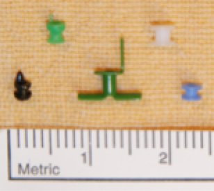 Figure: grommets of various sizes and designs. The white grommet at the top right is a Sheehy fluoroplastic collar button tube, the grommet most commonly used by Dr Smith.