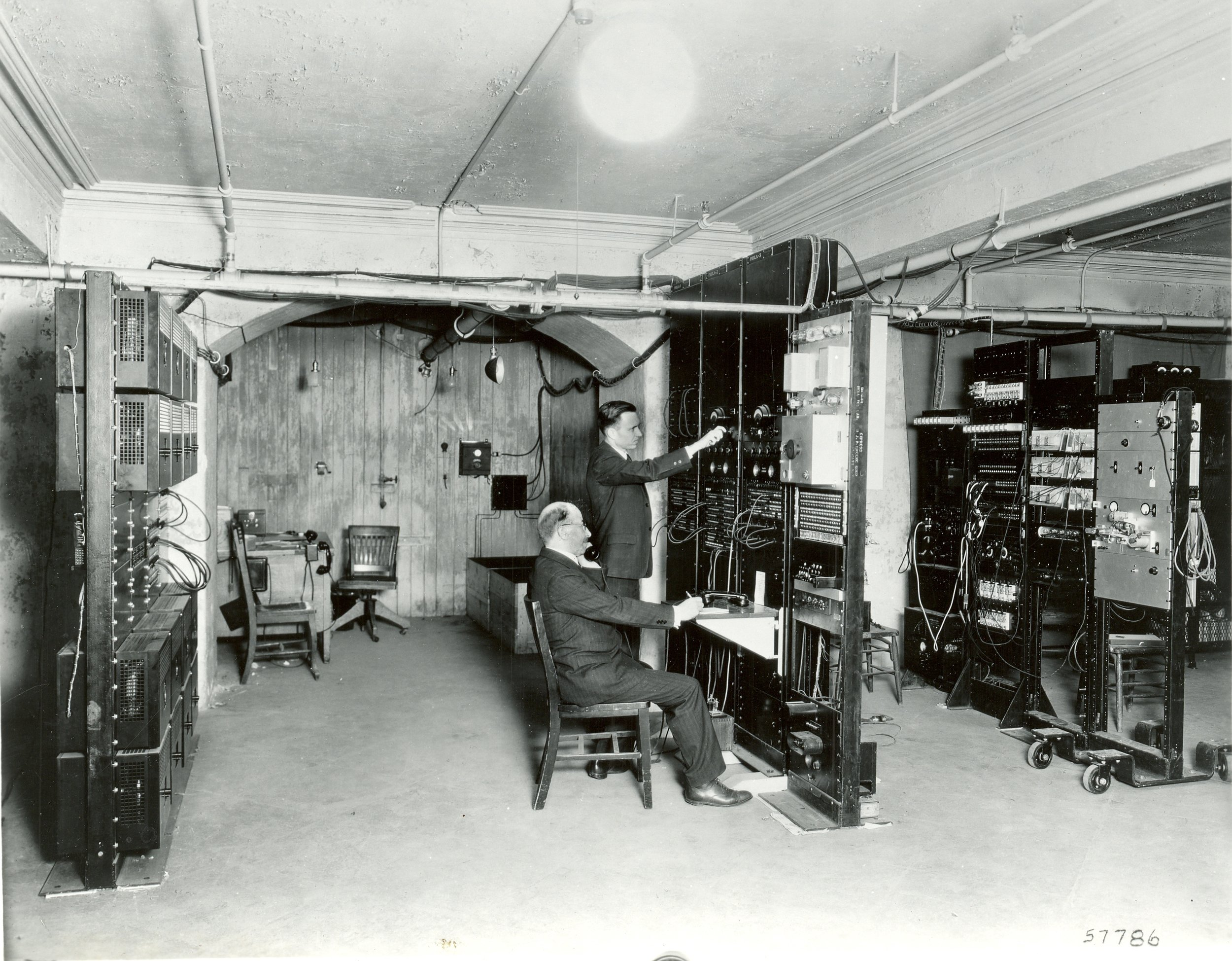 Two Bell Labs engineers sit in the Academy's basement, directly between the transmitting orchestra and the stereo speakers upstairs in the concert hall.