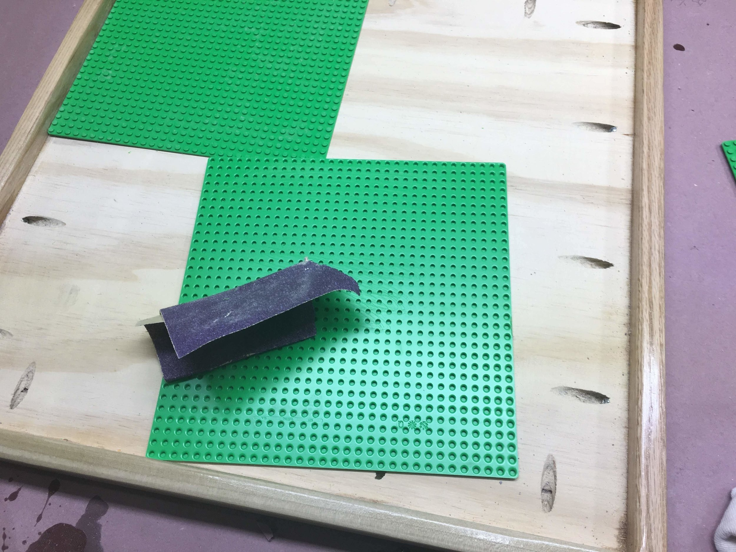 Here is me using the 60 grit sand paper to rough up the bottom of the Lego bases plates