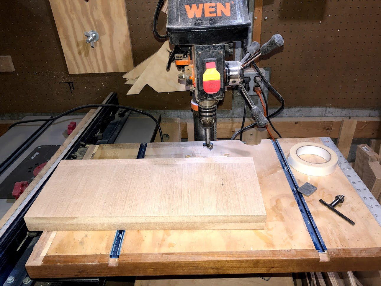 "Using my drill press with a 1"" forstner bit I stuck both side panels together and cut both holes at the same time."