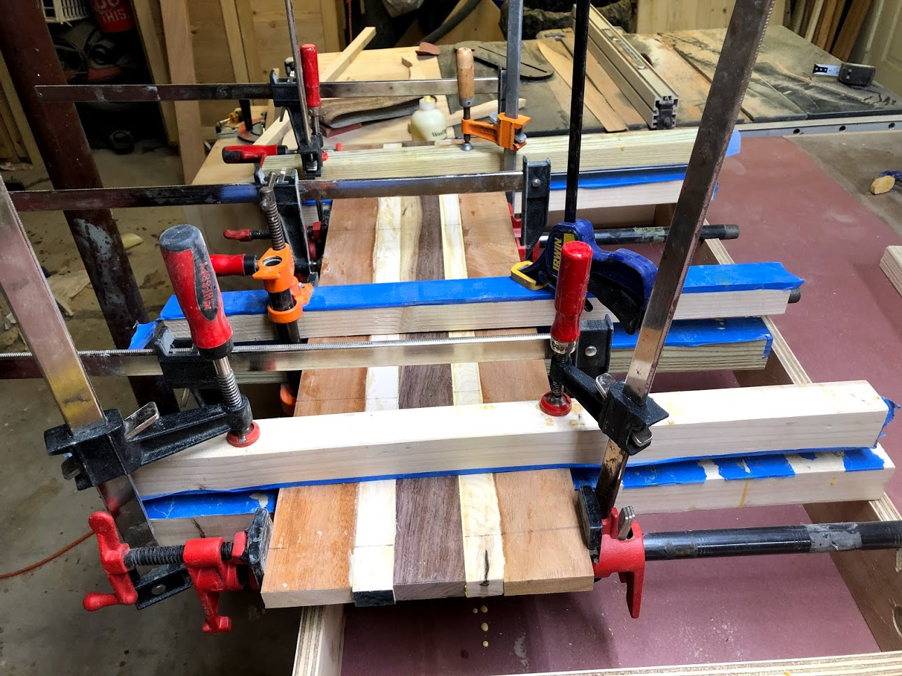 Here you can see the pipe clamps and the clamping cauls in my attempt at keeping the panel flat during the glue up.