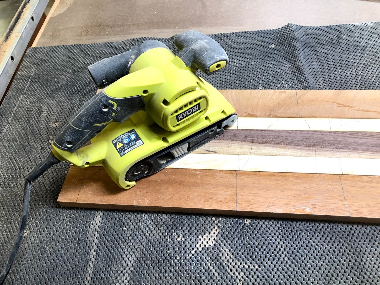 Here is my belt sander going to town on the panel, I drew pencil lines across all the edges of the mating pieces and when the pencil lines disappear I know the panel is flat.