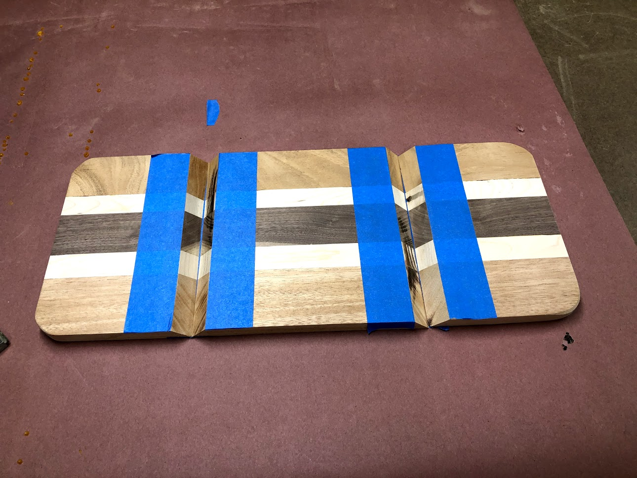 Here is the 3 pieces laying flat and painters tape on both sides of the mitered edge that will be receiving glue.