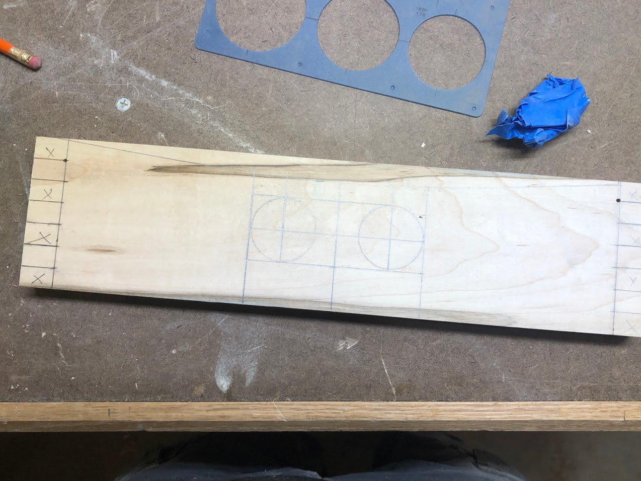 Here is the image of one of the sides with all the layout marks done for the handhold, which is basically 2 holes cut in the center of the board and then the rest of the material will be removed with a jigsaw.