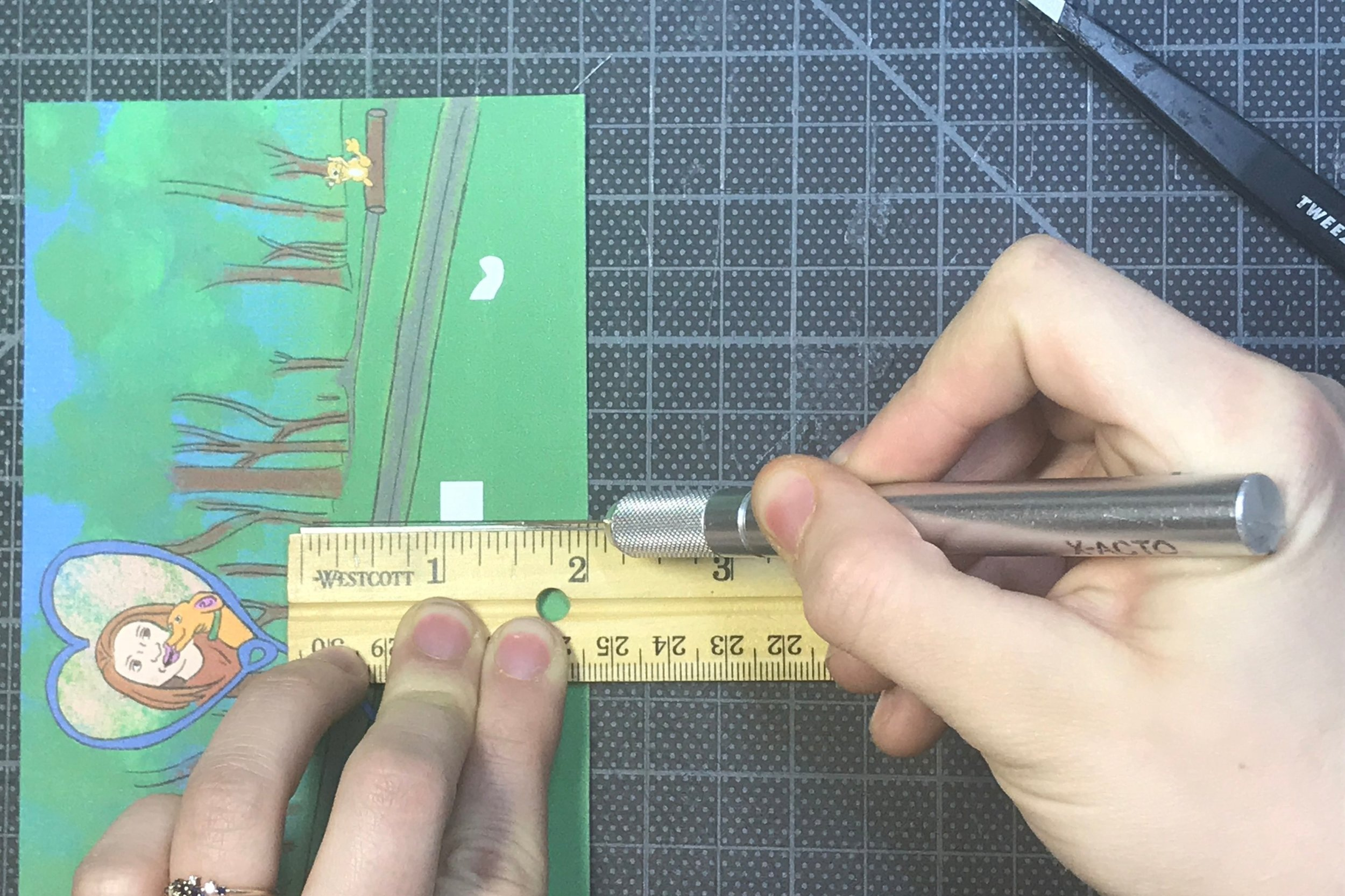 Cut the center line of your first postcard. The line is in the center of the card and runs two inches up from the bottom.