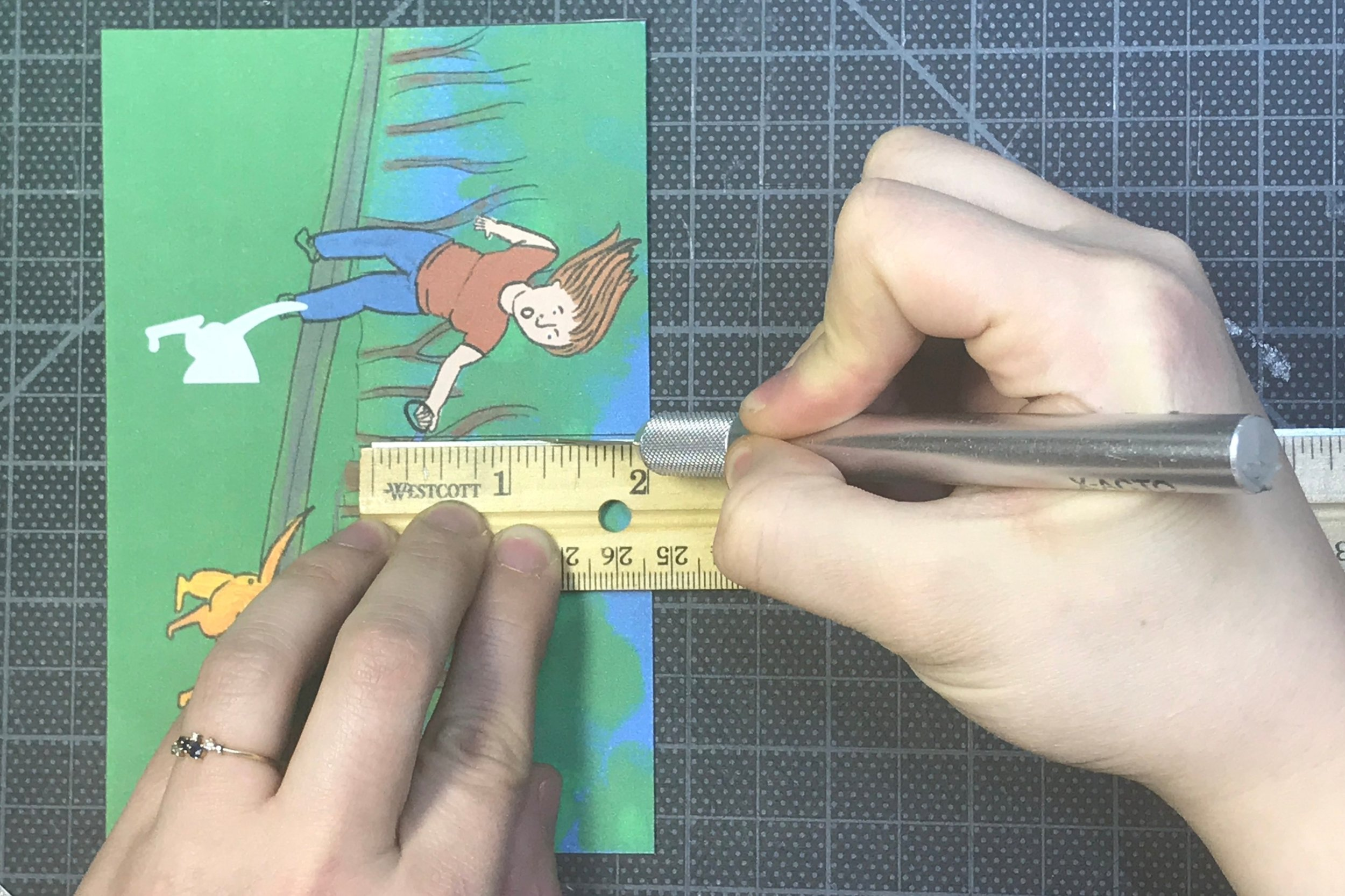 Cut the center line of your second postcard. The line is in the center of the card and runs two inches down from the top.