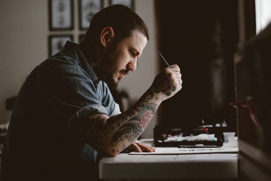 Man with dark hair and beard, and tattos working with paintbrush