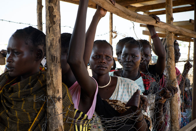 Women waited during a monthly distribution of food at a United Nations camp on the outskirts of Juba. Credit Kassie Bracken/The New York Times