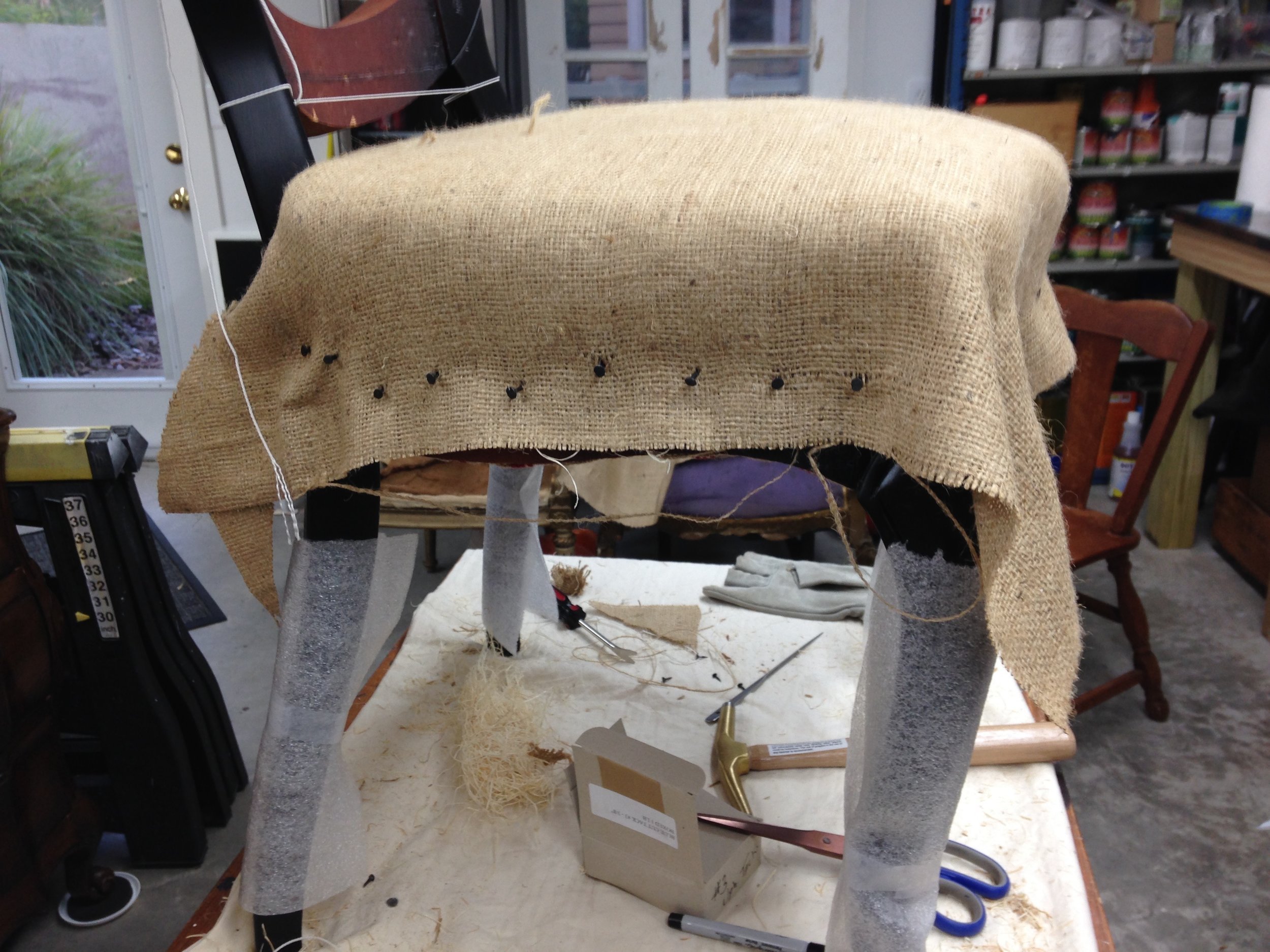 """The """"tacking-down"""" phase, over sculpted wood wool and hand-tied springs on webbing."""