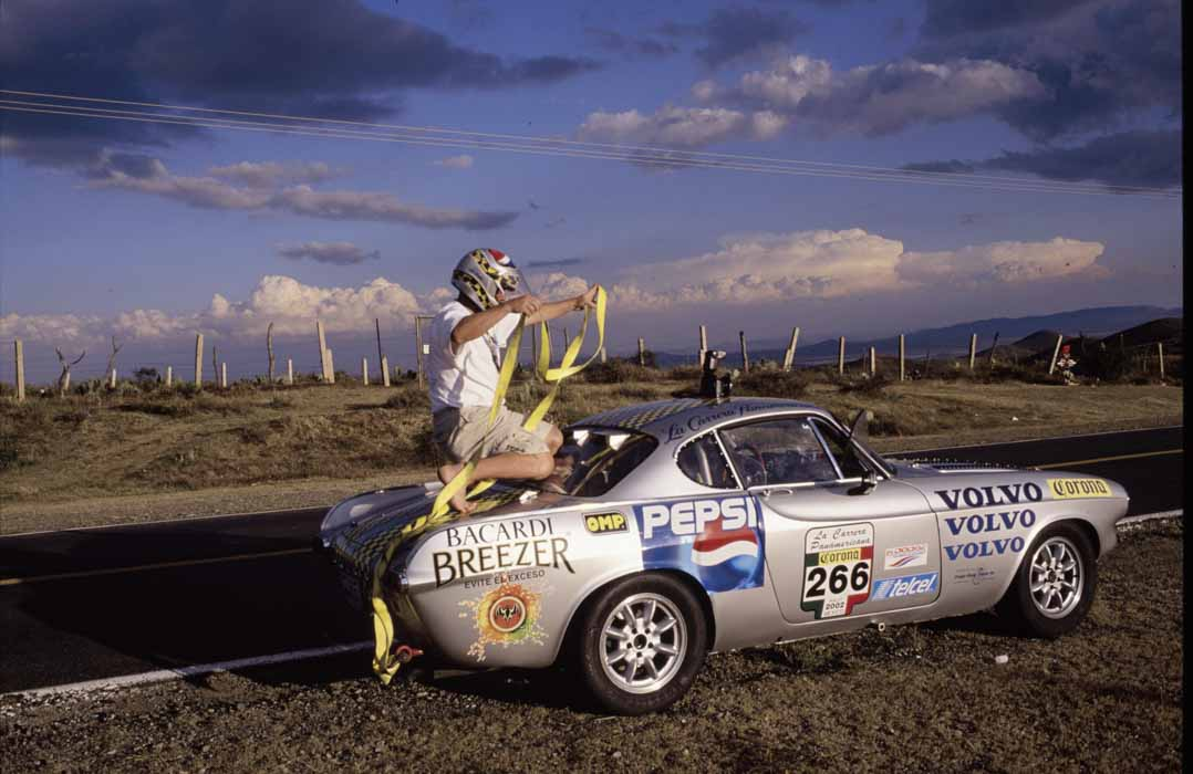 On the road and the new car is working very well …but for the Camera. Journalist & photographer extraordinaire Kenneth Olafuson gets credit for many of the photos herein and takes his chances @ La Carrera…here getting ready for a roof ride!!