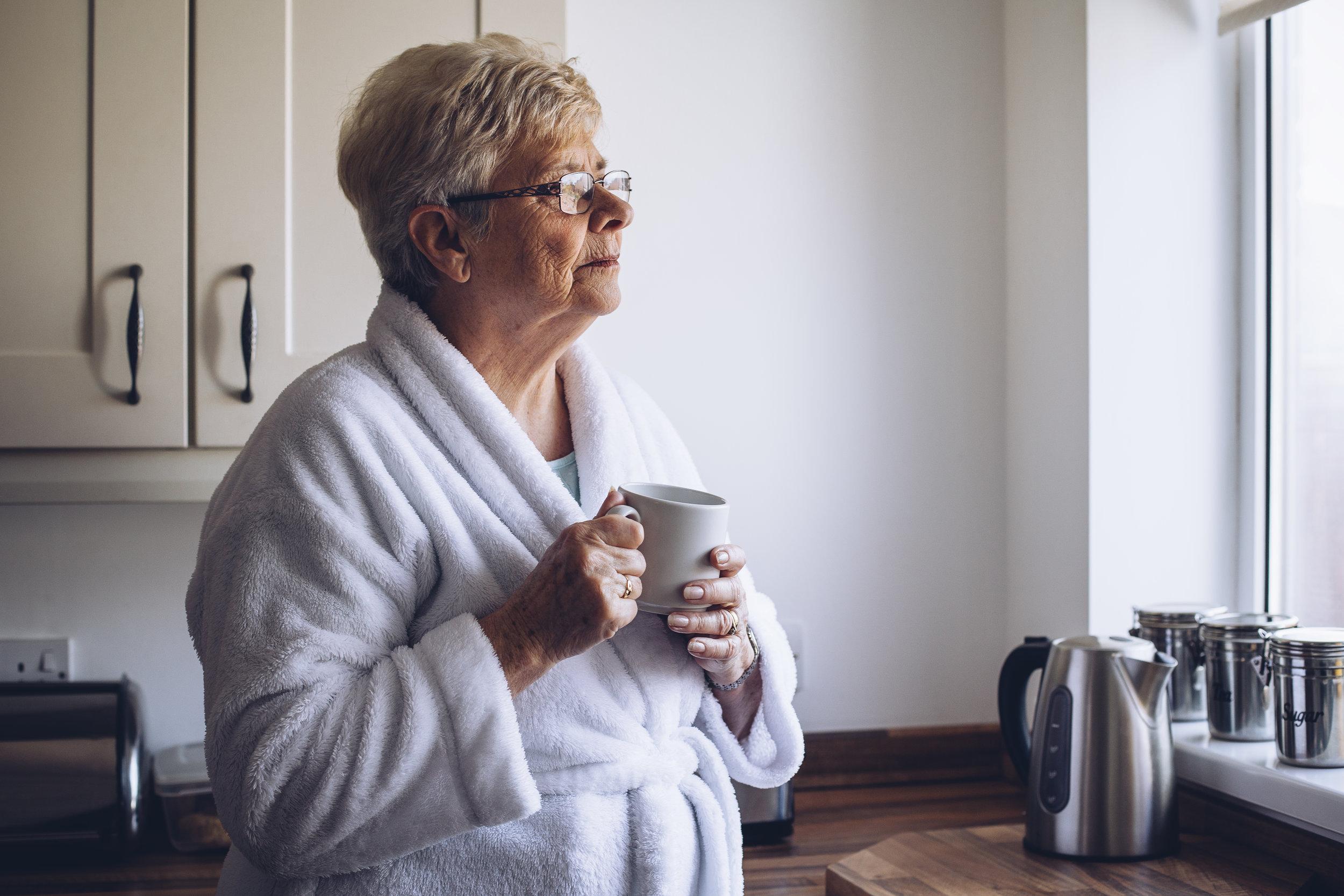 Senior-Woman-Looking-out-Window-602318816_5053x3369.jpeg
