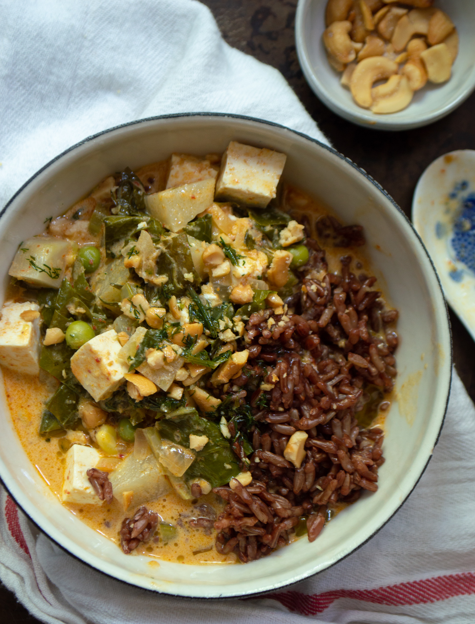 Red curry with red rice, tofu, kohlrabi root and leaves, and leftover frozen peas and corn, garnished with crushed cashews and dill herb oil