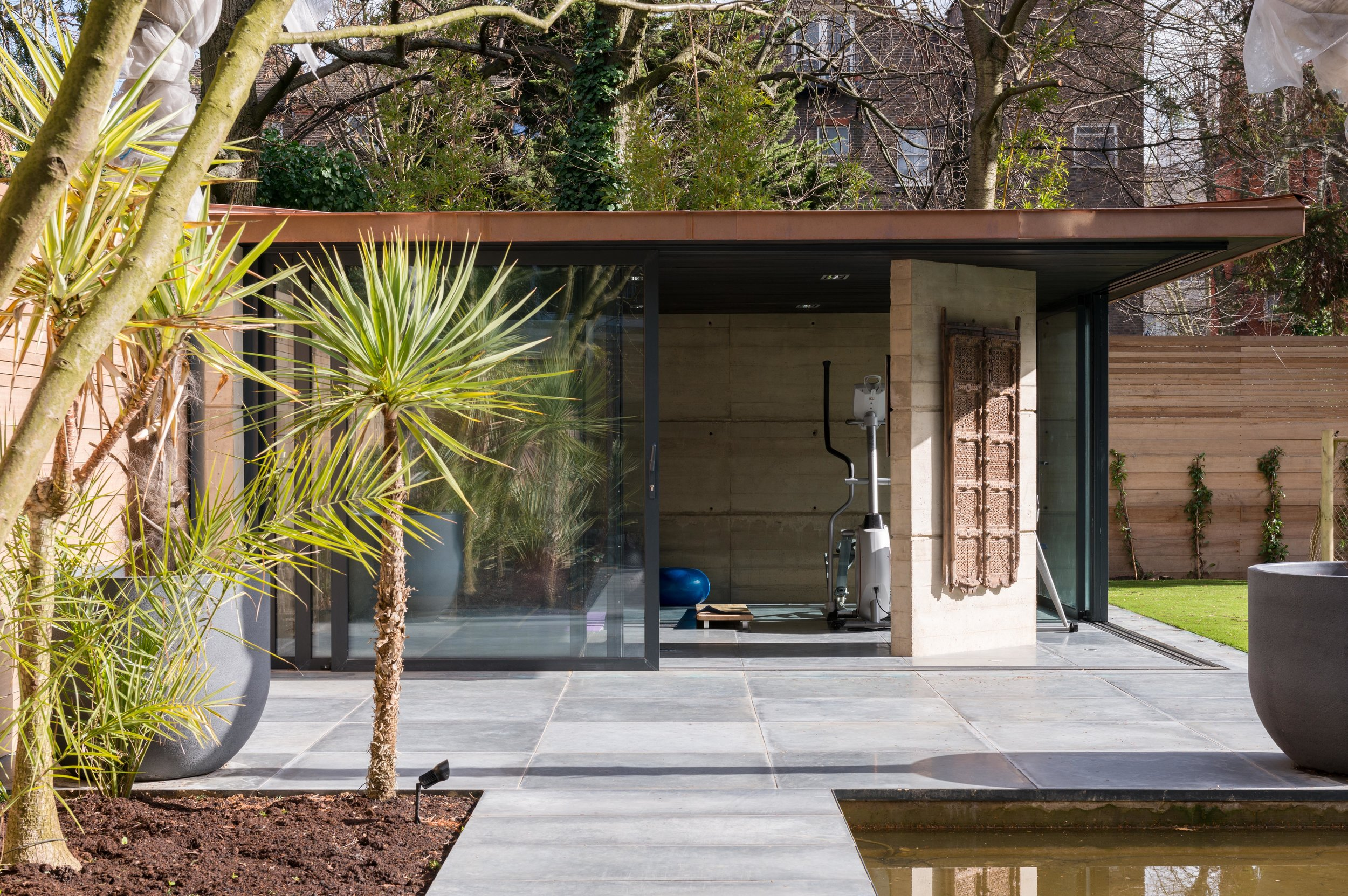 Yoga Pavilion   Hand-finished concrete and copper rear garden outbuilding beneath a tree canopy.