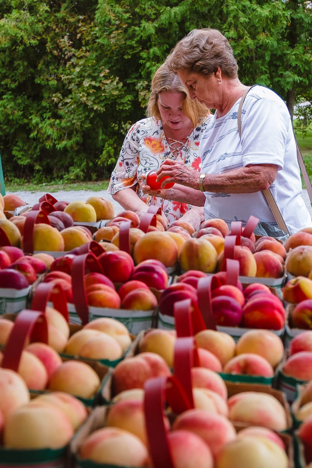 Women buying Ontario peaches