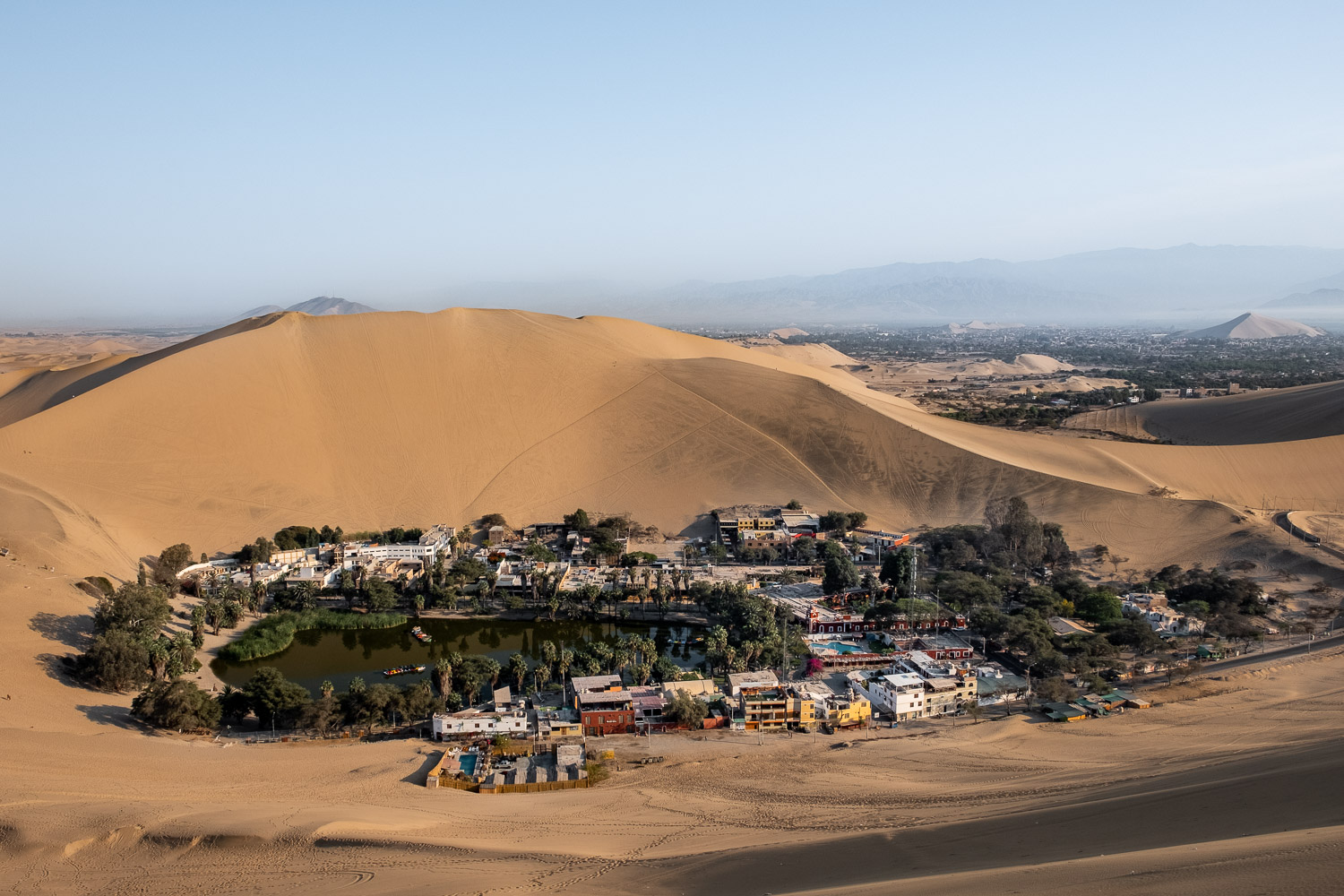 "The oasis town of Huacachina from the top of a sand dune, Peru. Travel photography and guide by © Natasha Lequepeys for ""And Then I Met Yoko"". #peru #ica #huacachina #photoblog #travelblog #travelphotography #landscapephotography #travelitinerary #fujifilm #sanddunes #desert #sunset #sandboarding #streetfood #foodphotography #oasis #backpacker #winery #travel #huacachinatours"