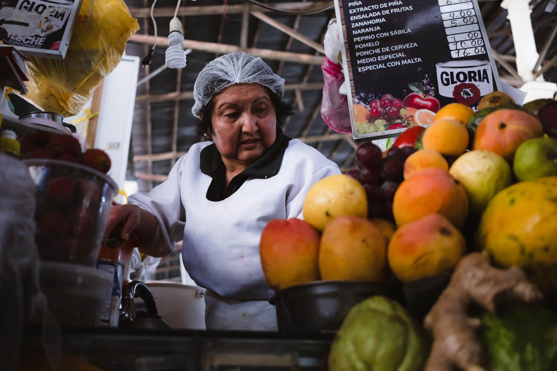 "A woman making fresh juice in the San Pedro Market. Travel photography and guide by © Natasha Lequepeys for ""And Then I Met Yoko"". #cusco #peru #travelguide #photoblog #travelblog #travelphotography #landscapephotography #travelitinerary #fujifilm #southamerica #peruitinerary #sacredvalley #incasights #machupicchu #cusco #ancientruins #incatrail #ValleSagrado #travel #cuscoitinerary"