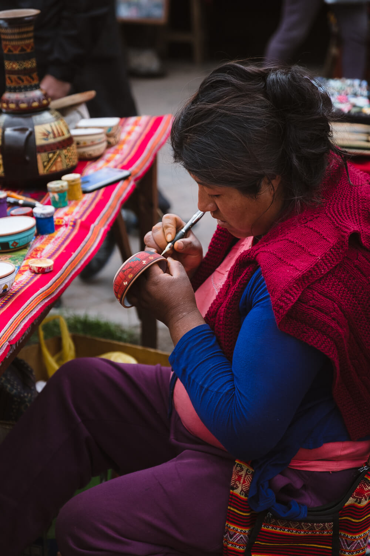 "A woman pains jewelry in the market, Raqch'i. Travel photography and guide by © Natasha Lequepeys for ""And Then I Met Yoko"". #peru #sacredvalley #cusco #laketiticaca #belmondandeanexplorer #perurail #perutrain #luxurytravel #sleepertrain #photoblog #travelblog #travelphotography #fujifilm #andes #travel #travelperu #cuscotolaketiticaca #spiritofthelake #belmond #puno #southamerica"