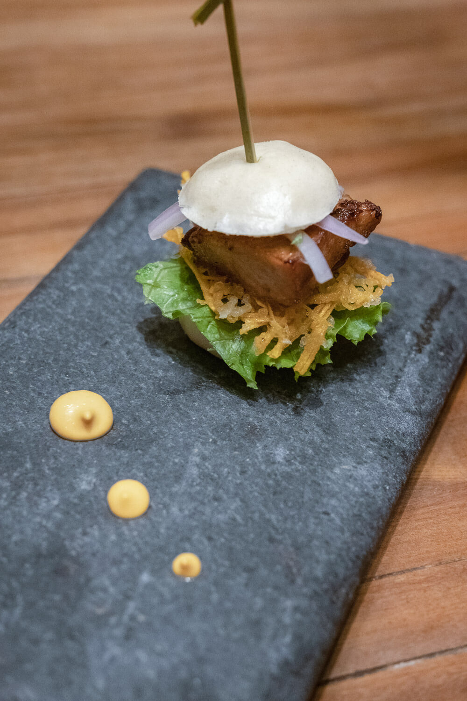 Maido: Chicharron Sandwich - Steamed buns, pork belly, kimchee emulsion, creole sauce