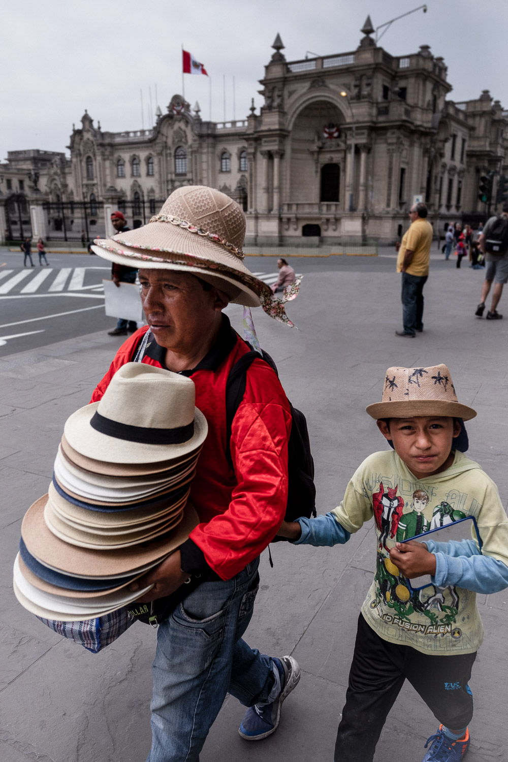"""A man selling hats walks with his son in Lima, Peru. Travel photography and guide by © Natasha Lequepeys for """"And Then I Met Yoko"""". #photoblog #travelblog #travelperu"""