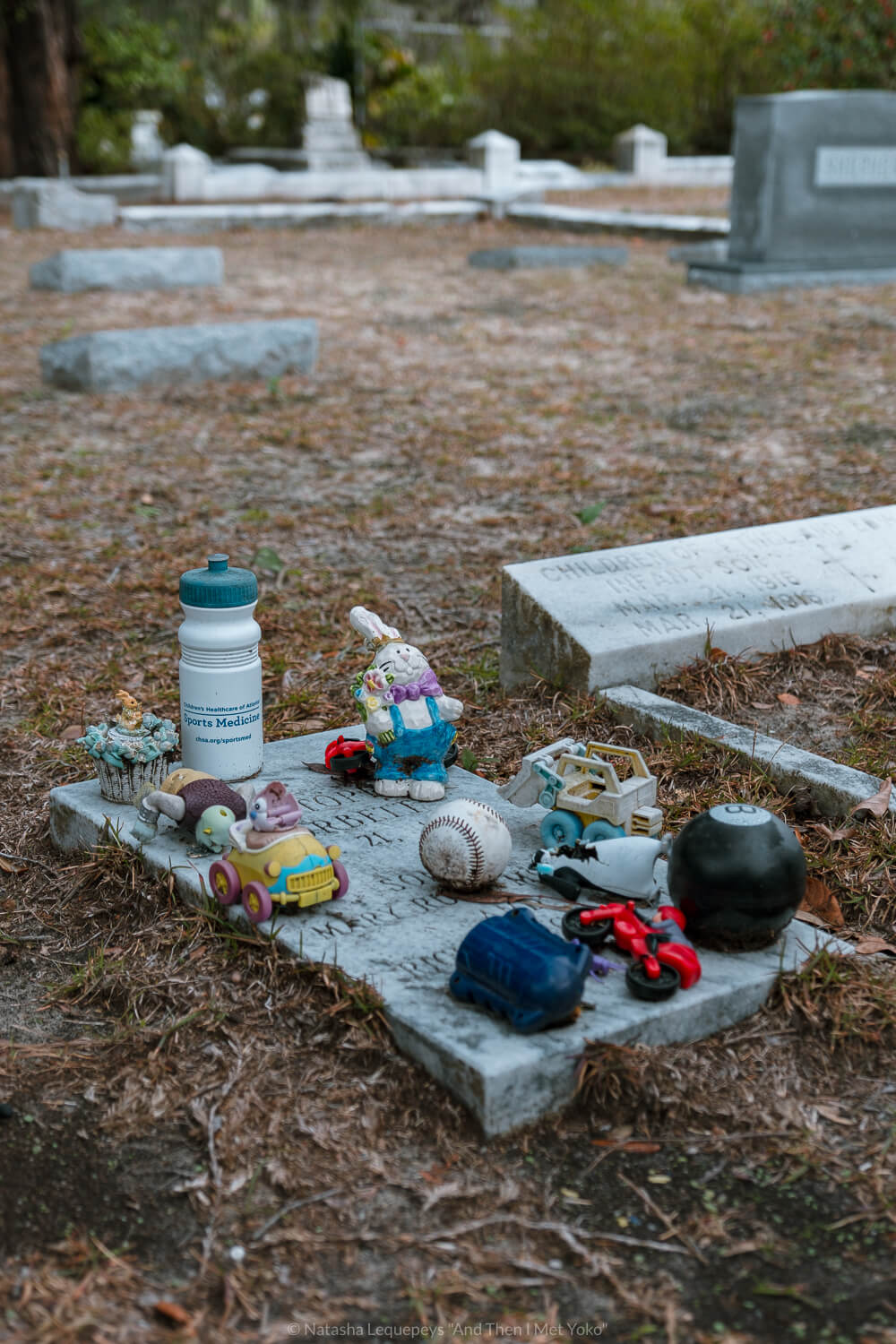 """Children's toys on a grave at Bonaventure Cemetery in Savannah, Georgia. Travel photography and guide by © Natasha Lequepeys for """"And Then I Met Yoko"""". #bonaventurecemetery #savannah #travelguide #travelblog #travelphotography #fujifilm"""