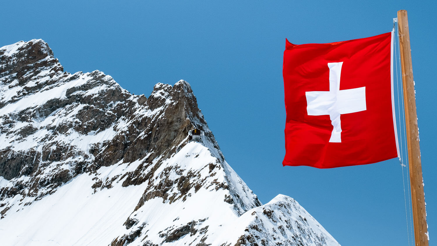 "The Swiss flag and mountain peaks Jungfraujoch, Switzerland. Travel photography and guide by © Natasha Lequepeys for ""And Then I Met Yoko"". #wengen #jungfraujoch #travelguide #switzerland #travelphotography"