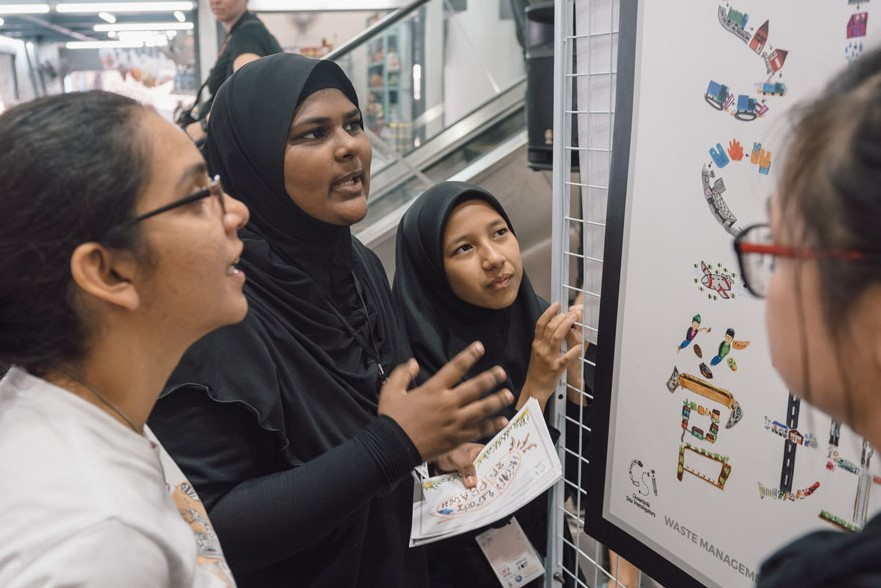 A student explains her illustrated typography design based on waste management at Chowrasta Market during an on-site exhibition.