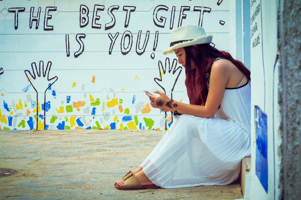 """a girl sitting, looking at her phone in front of a wall saying """"The best gift is you."""""""