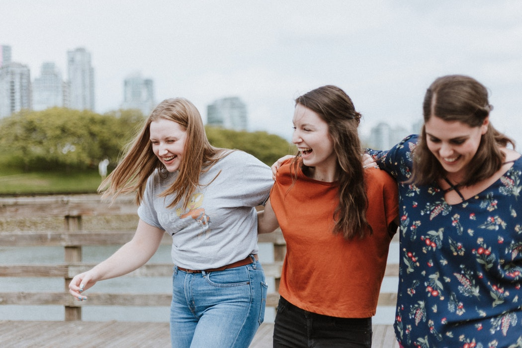 three female friends walking and laughing in city park