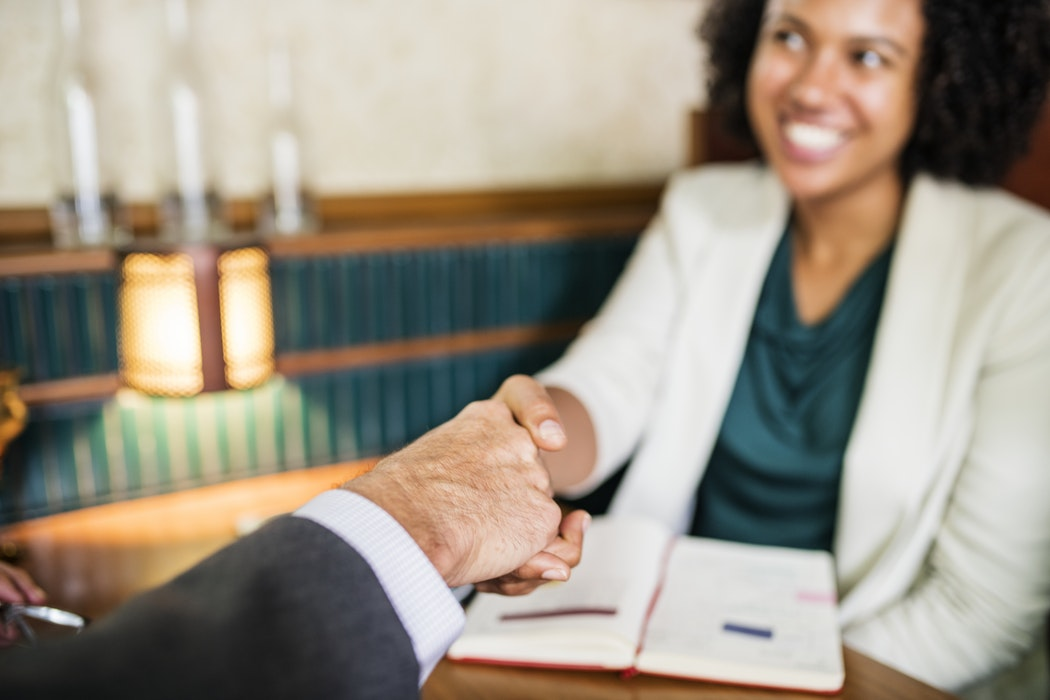 black woman smiling and white man shaking hands