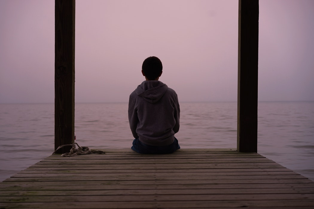 boy sitting on a peaceful dock at dusk